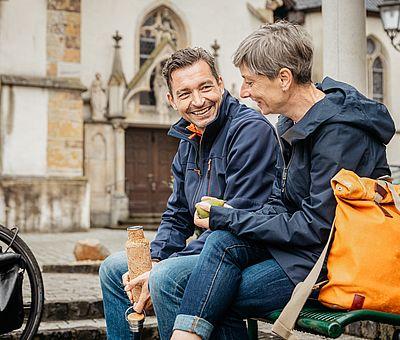 Zwei Personen sitzen an einer Kirche